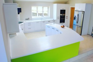 white hi-gloss kitchen with curved lime green panelling and White Corian worktop
